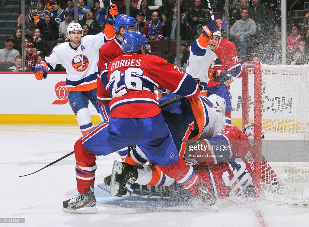 Josh Gorges #26 of the Montreal Canadiens pushes Mark Streit #2 of the New York Islanders into goalie Peter Budaj #30 on March 17, 2012 at the Bell Centre in Montreal, Quebec, Canada. The New York Islanders scored on the play.