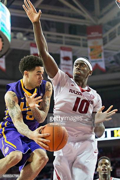 Josh Gray of the LSU Tigers makes a pass out from under the basket while being defended by Bobby Portis of the Arkansas Razorbacks at Bud Walton...