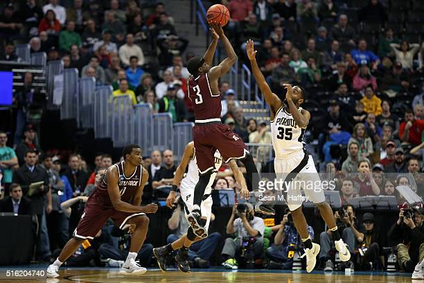 Josh Hagins of the Arkansas Little Rock Trojans makes a shot over Rapheal Davis of the Purdue Boilermakers during the first round of the 2016 NCAA...
