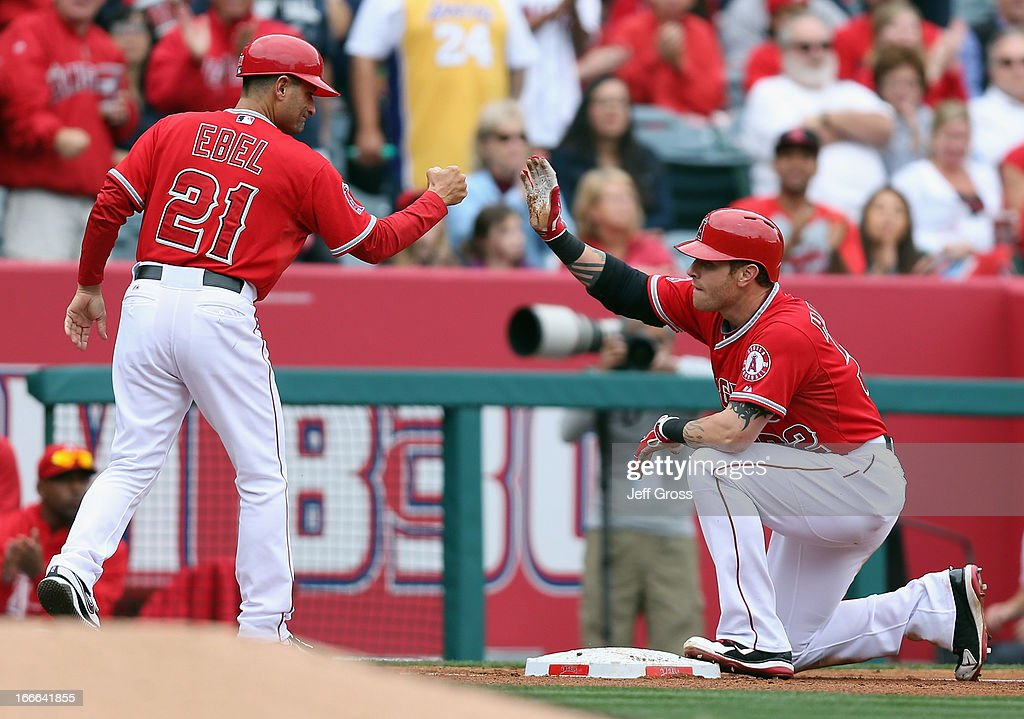 Josh Hamilton (R) #32 of the Los Angeles Angels of Anaheim is congratulated by third base coach Dino Ebel #21 after hitting a triple in the third inning against the Houston Astros at Angel Stadium of Anaheim on April 14, 2013 in Anaheim, California.