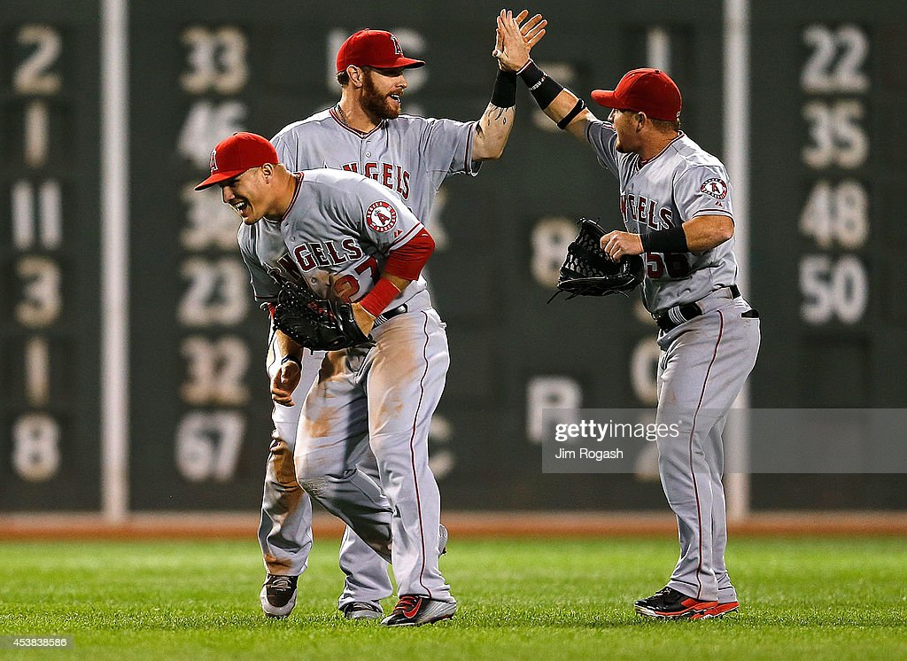 Josh Hamilton #32, <a gi-track='captionPersonalityLinkClicked' href=/galleries/search?phrase=Kole+Calhoun&family=editorial&specificpeople=9008672 ng-click='$event.stopPropagation()'>Kole Calhoun</a> #56, and <a gi-track='captionPersonalityLinkClicked' href=/galleries/search?phrase=Mike+Trout&family=editorial&specificpeople=7091306 ng-click='$event.stopPropagation()'>Mike Trout</a> #27 of the Los Angeles Angels of Anaheim celebrate a 4-3 win against the Boston Red Sox at Fenway Park on August 19, 2014 in Boston, Massachusetts.