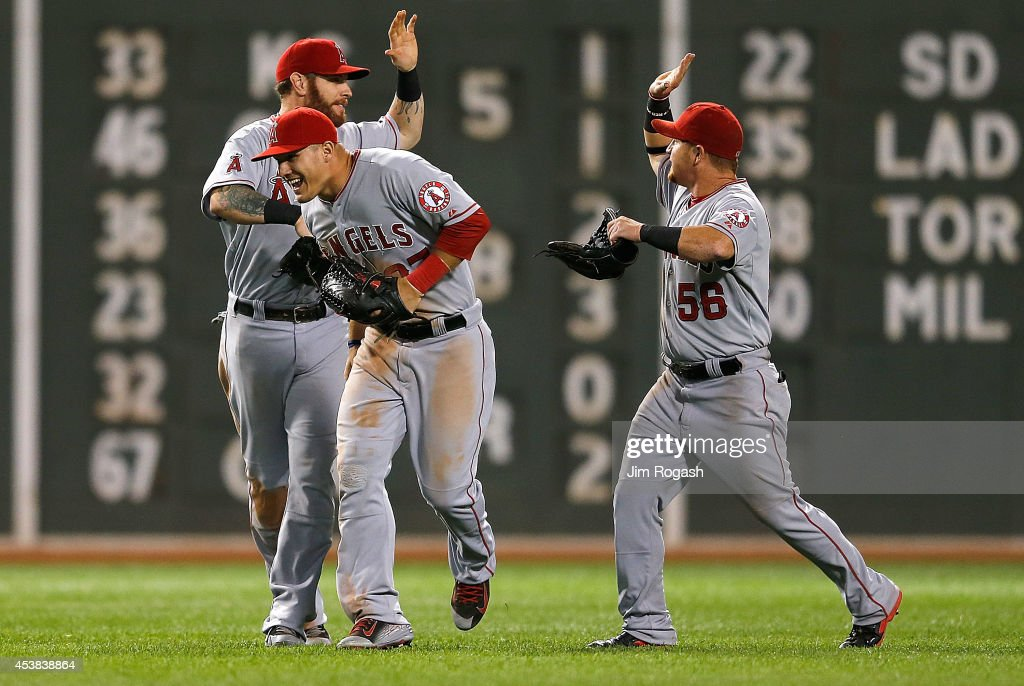 Josh Hamilton Kole Calhoun and Mike Trout of the Los Angeles Angels of Anaheim celebrate a 43 win against the Boston Red Sox at Fenway Park on August...