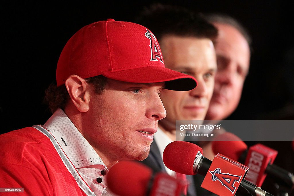 Josh Hamilton #32 of the Los Angeles Angels of Anaheim aswers questions from the media as General Manager Jerry Dipoto and Manager Mike Scioscia look on during the press conference introducing Hamilton as the team's newest member at ESPN Zone at Downtown Disney on December 15, 2012 in Anaheim, California.