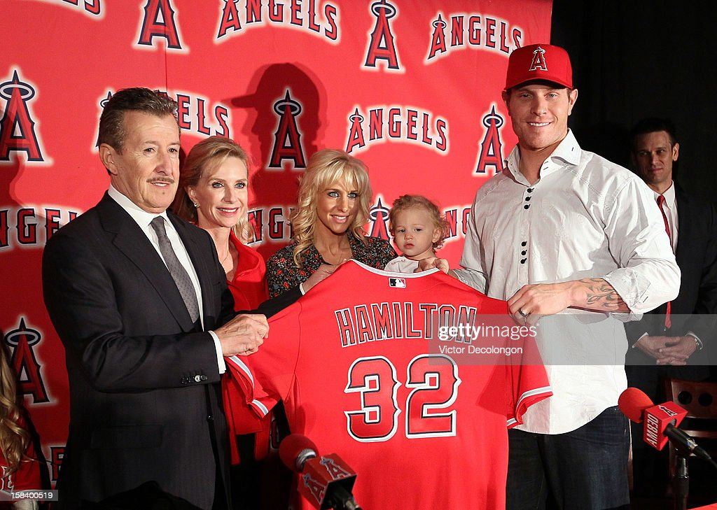 Josh Hamilton #32 of the Los Angeles Angels of Anaheim (R) holds up his new jersey with Angels Owner Arte Moreno during the press conference introducing Hamilton as the team's newest player as wife Katie, daughter Stella Faith and Carole Moreno look on from the background at ESPN Zone at Downtown Disney on December 15, 2012 in Anaheim, California.