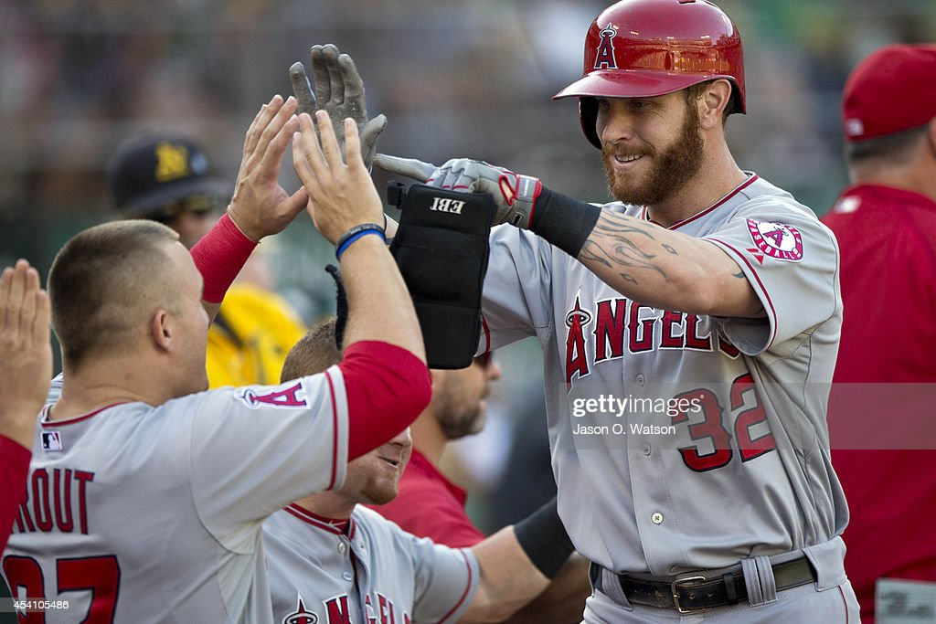 Josh Hamilton #32 of the Los Angeles Angels of Anaheim is congratulated by <a gi-track='captionPersonalityLinkClicked' href=/galleries/search?phrase=Mike+Trout&family=editorial&specificpeople=7091306 ng-click='$event.stopPropagation()'>Mike Trout</a> #27 in the dugout after hitting a two run home run against the Oakland Athletics during the third inning at O.co Coliseum on August 24, 2014 in Oakland, California.