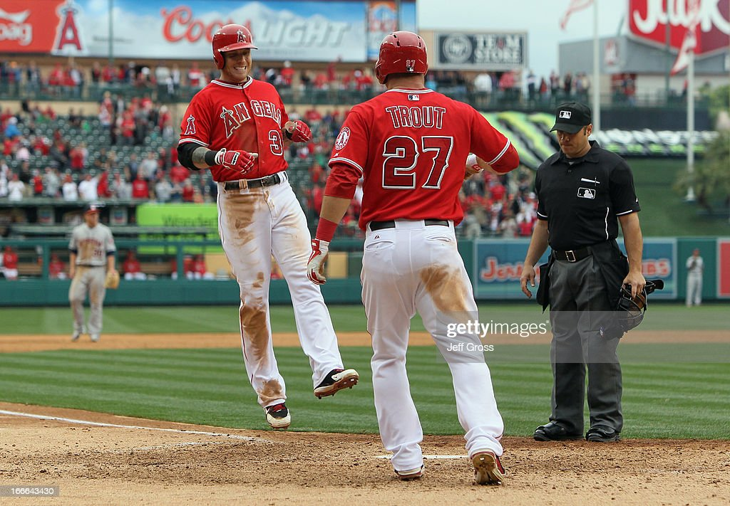 Josh Hamilton #32 of the Los Angeles Angels of Anaheim is met at home plate by <a gi-track='captionPersonalityLinkClicked' href=/galleries/search?phrase=Mike+Trout&family=editorial&specificpeople=7091306 ng-click='$event.stopPropagation()'>Mike Trout</a> #27 after hitting a two-run home run in the eighth inning against the Houston Astros, as umpire <a gi-track='captionPersonalityLinkClicked' href=/galleries/search?phrase=Mark+Wegner&family=editorial&specificpeople=226706 ng-click='$event.stopPropagation()'>Mark Wegner</a> looks on at Angel Stadium of Anaheim on April 14, 2013 in Anaheim, California. The Angels defeated the Astros 4-1.