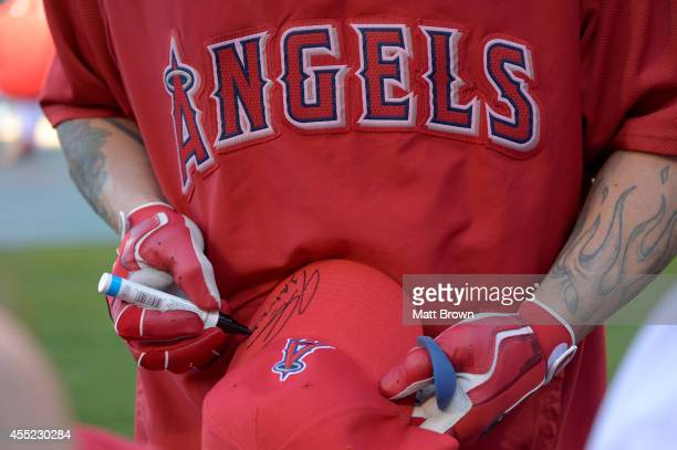 Josh Hamilton of the Los Angeles Angels of Anaheim signs an autograph on a hat before the game against the Miami Marlins on August 26 2014 at Angel...