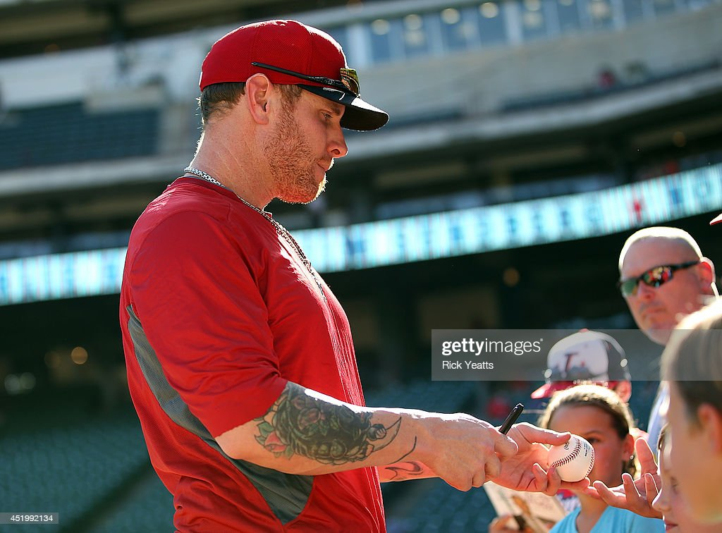 Josh Hamilton #32 of the Los Angeles Angels of Anaheim signs autographs before the game against the Texas Rangers at Globe Life Park in Arlington on July 10, 2014 in Arlington, Texas.