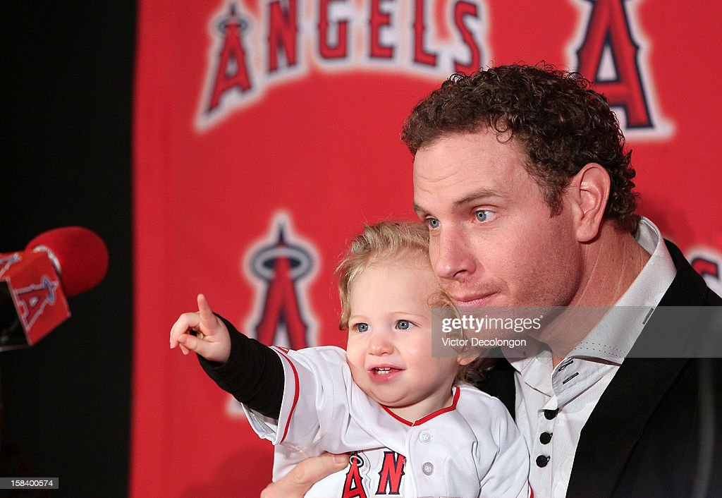 Josh Hamilton #32 of the Los Angeles Angels of Anaheim sits his daughter Stella Faith on his lap during the press conference introducing Hamilton as the team's newest member at ESPN Zone at Downtown Disney on December 15, 2012 in Anaheim, California.