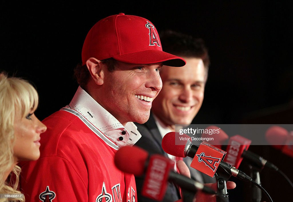 Josh Hamilton #32 of the Los Angeles Angels of Anaheim smiles during the press conference introducing Hamilton as the team's newest player as Angels General Manager Jerry Dipoto (R) and wife Katie look on at ESPN Zone at Downtown Disney on December 15, 2012 in Anaheim, California.