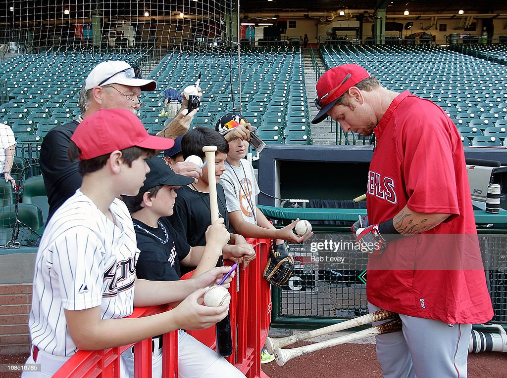 Josh Hamilton #32 of the Los Angeles Angels signs autographs for fans during batting practice before playing the Houston Astros at Minute Maid Park on May 8, 2013 in Houston, Texas.