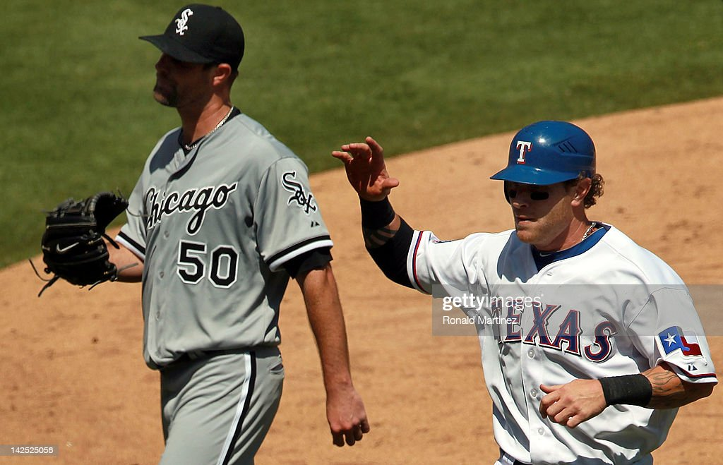 Josh Hamilton #32 of the Texas Rangers celebrates a run in front of <a gi-track='captionPersonalityLinkClicked' href=/galleries/search?phrase=John+Danks&family=editorial&specificpeople=835613 ng-click='$event.stopPropagation()'>John Danks</a> #50 of the Chicago White Sox during the Opening Day game at Rangers Ballpark in Arlington on April 6, 2012 in Arlington, Texas.