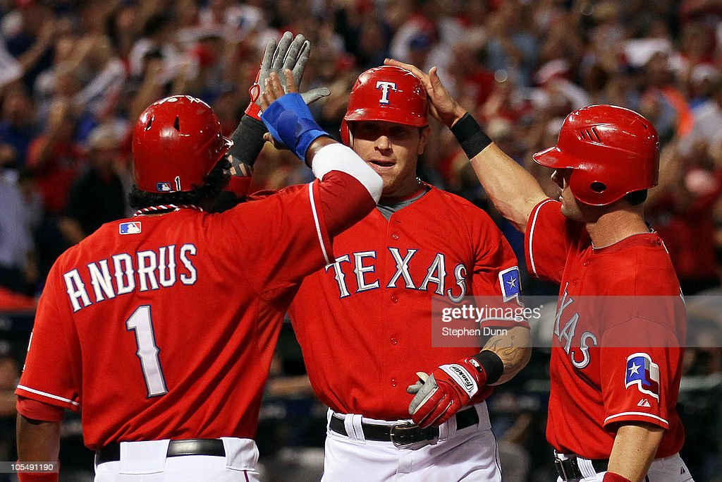 Josh Hamilton of the Texas Rangers celebrates with Elvis Andrus and Michael Young after Hamilton's three run home run in the first inning against the...
