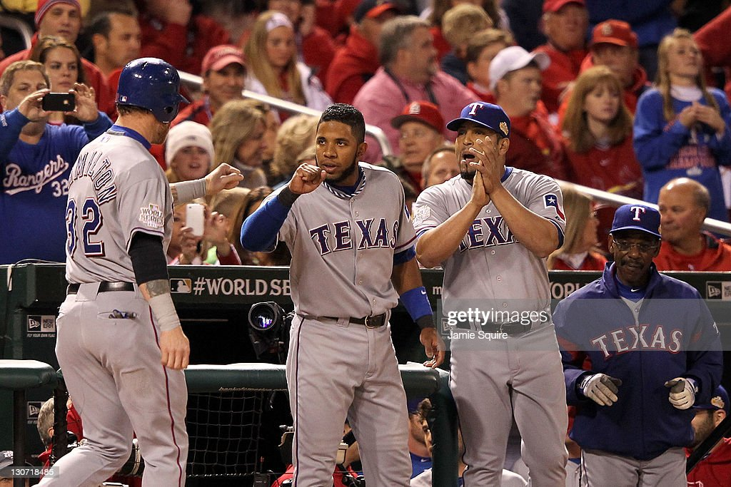 Josh Hamilton #32 of the Texas Rangers celebrates with <a gi-track='captionPersonalityLinkClicked' href=/galleries/search?phrase=Elvis+Andrus&family=editorial&specificpeople=4845974 ng-click='$event.stopPropagation()'>Elvis Andrus</a> #1, <a gi-track='captionPersonalityLinkClicked' href=/galleries/search?phrase=Yorvit+Torrealba&family=editorial&specificpeople=212721 ng-click='$event.stopPropagation()'>Yorvit Torrealba</a> #8 and manager <a gi-track='captionPersonalityLinkClicked' href=/galleries/search?phrase=Ron+Washington&family=editorial&specificpeople=225012 ng-click='$event.stopPropagation()'>Ron Washington</a> after scoring on an RBI double by Michael Young #10 in the first inning during Game Seven of the MLB World Series against the St. Louis Cardinals at Busch Stadium on October 28, 2011 in St Louis, Missouri.
