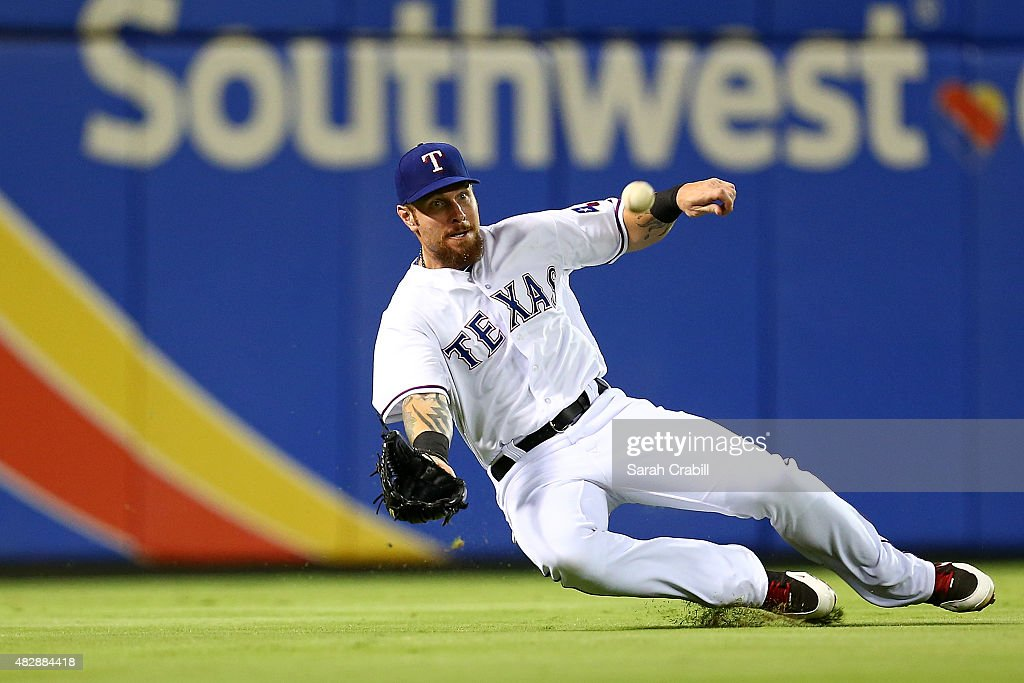 Josh Hamilton #32 of the Texas Rangers makes a sliding catch in the seventh inning during a game against the Houston Astros at Globe Life Park in Arlington on August 3, 2015 in Arlington, Texas.