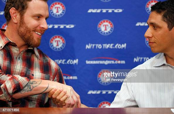 Josh Hamilton outfielder for the Texas Rangers shakes hands with Jon Daniels Texas Rangers President of Baseball Operations and General Manager at...