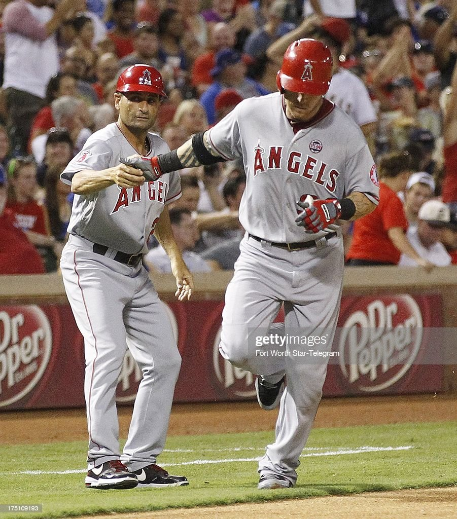 Josh Hamilton, right, of the Los Angeles Angels is congratulated by third base coach Dino Ebel after a seventh-inning solo home run against the Texas Rangers at the Rangers Ballpark in Arlington on Wednesday July 31, 2013, in Arlington, Texas. The Rangers won, 2-1.