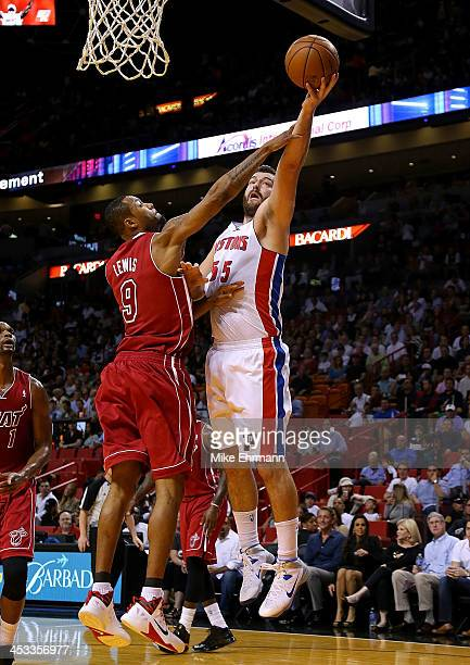 Josh Harrellson of the Detroit Pistons shoots over Rashard Lewis of the Miami Heat during a game at American Airlines Arena on December 3 2013 in...