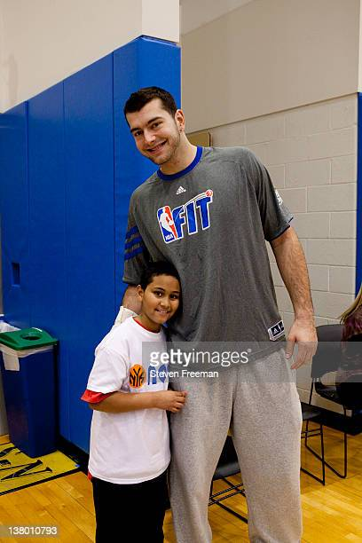 Josh Harrellson of the New York Knicks poses with a kid during a New York Knicks Fit Clinic on January 30 2012 at the Madison Square Garden Training...