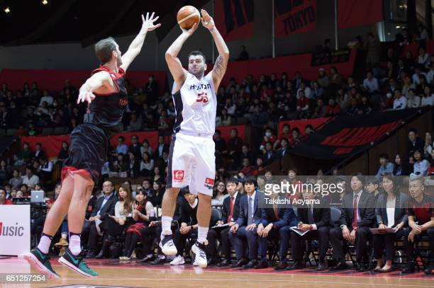 Josh Harrellson of the Osaka Evessa tries to shoot under pressure from Trent Plaisted of the Alvark Tokyo during the B League match between Alvark...