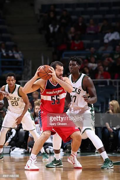Josh Harrellson of the Washington Wizards handles the ball against Johnny O'Bryant III of the Milwaukee Bucks during a preseason game on October 17...