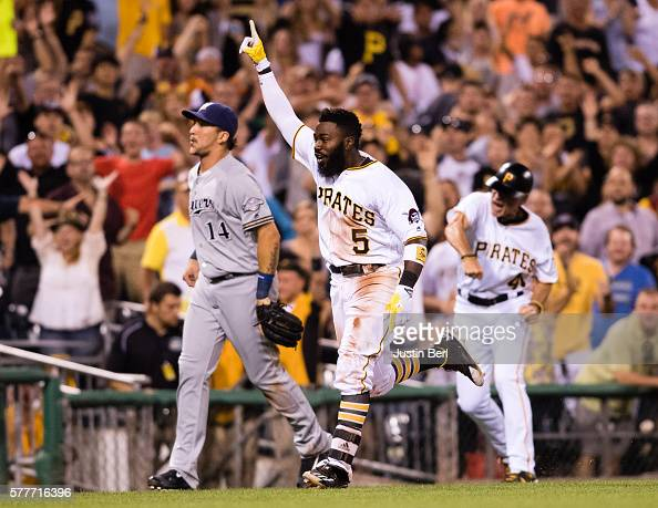 Josh Harrison of the Pittsburgh Pirates celebrates as he heads towards home plate after hitting a triple and comes in to score on a throwing error by...