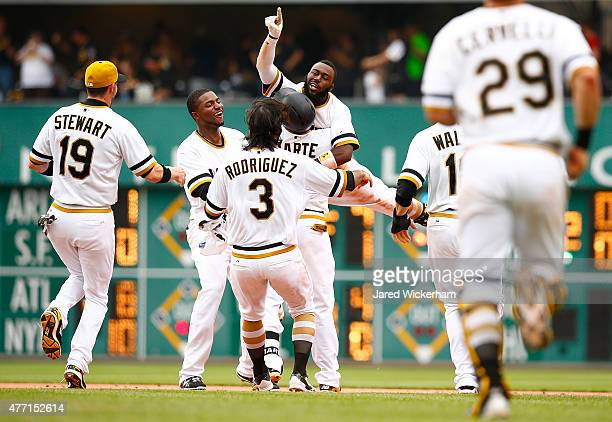 Josh Harrison of the Pittsburgh Pirates celebrates his gamewinning RBI single in the 11th inning with teammates Starling Marte Sean Rodriguez and...