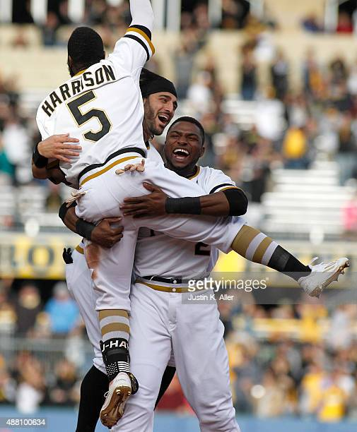Josh Harrison of the Pittsburgh Pirates celebrates with Sean Rodriguez and Gregory Polanco after hitting a walk off single in the eleventh inning...