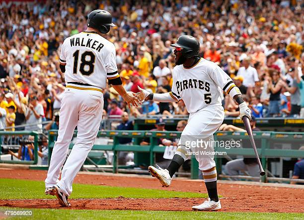 Josh Harrison of the Pittsburgh Pirates celebrates with teammate Neil Walker after both scoring in the fifth inning against the Cleveland Indians...