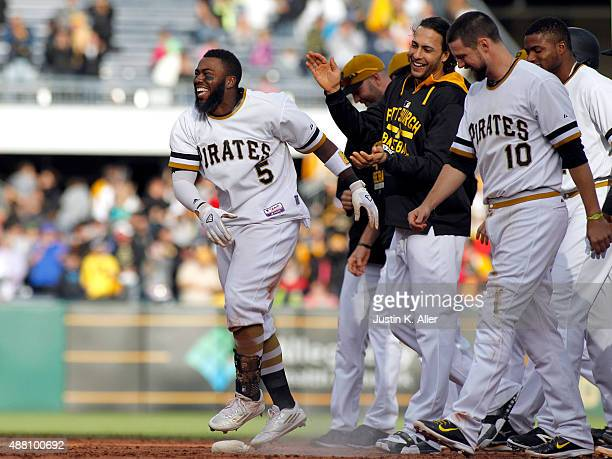 Josh Harrison of the Pittsburgh Pirates celebrates with teammates after hitting a walk off single in the eleventh inning during the game against the...