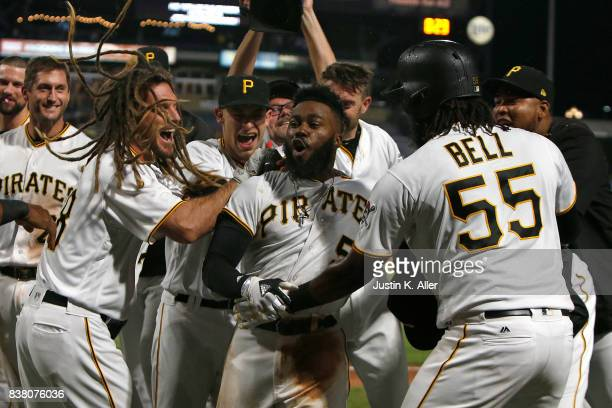 Josh Harrison of the Pittsburgh Pirates celebrates with teammates after hitting a walk off home run in the tenth inning breaking up a no hitter...