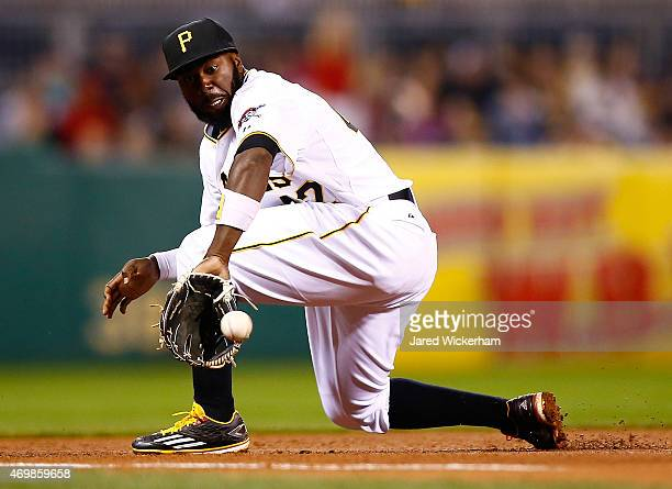Josh Harrison of the Pittsburgh Pirates fields a ground ball down the third base line in the ninth inning against the Detroit Tigers while wearing...