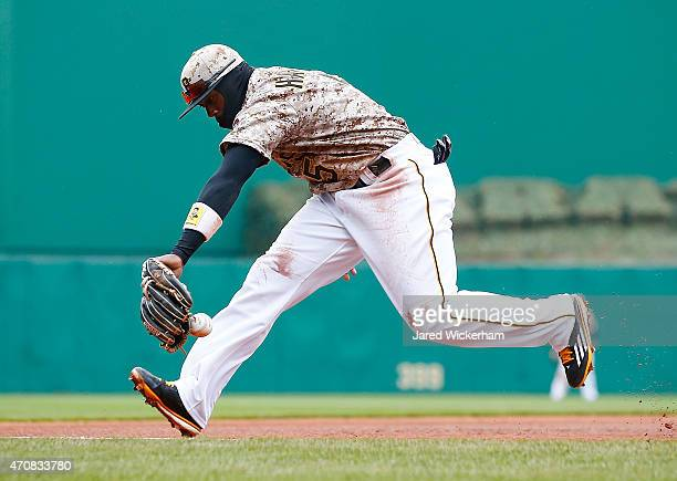 Josh Harrison of the Pittsburgh Pirates fields a ground ball down the third base line in the fourth inning against the Chicago Cubs during the game...