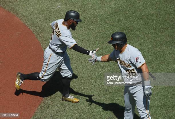 Josh Harrison of the Pittsburgh Pirates is congratulated by Jose Osuna after scoring a run in the first inning during MLB game action against the...