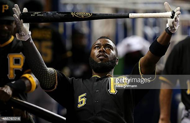 Josh Harrison of the Pittsburgh Pirates limbos under his bat during a game against the Miami Marlins at Marlins Park on August 26 2015 in Miami...