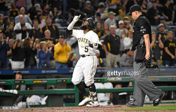 Josh Harrison of the Pittsburgh Pirates points to the sky as he crosses home plate after hitting a solo home run in the seventh inning during the...