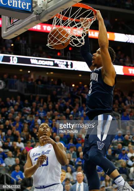 Josh Hart of the Villanova Wildcats dunks as Desi Rodriguez of the Seton Hall Pirates looks on during the first half of an NCAA college basketball...