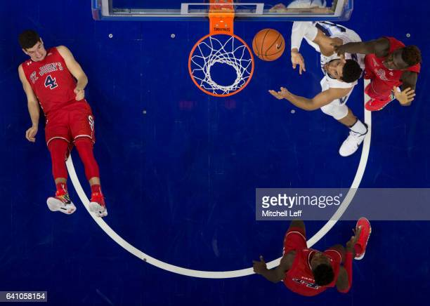 Josh Hart of the Villanova Wildcats shoots the ball against Bashir Ahmed of the St John's Red Storm as Federico Mussini and Kassoum Yakwe of the St...