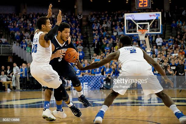Josh Hart of the Villanova Wildcats tries to drives to the basket between Maurice Watson Jr #10 and Khyri Thomas of the Creighton Bluejays during...