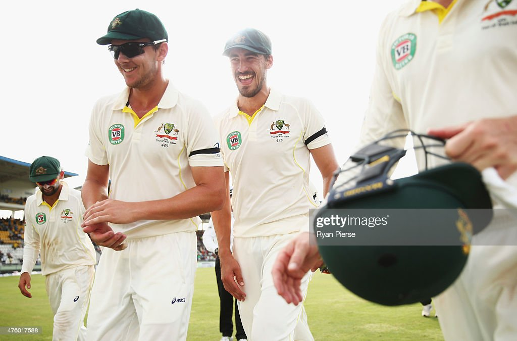 Josh Hazlewood and Mitchell Starc of Australia celebrate after bowling West Indies out for 216 in their second innings during day three of the First...