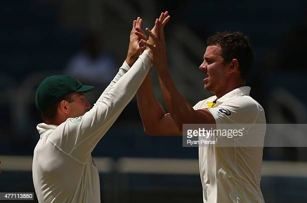Josh Hazlewood and Shaun Marsh of Australia of Australia celebrate after taking the wicket of Darren Bravo of West Indies during day four of the...