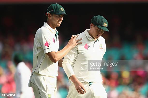 Josh Hazlewood of Australia comforts Matt Renshaw of Australia as he leaves the field after being struck on the helmet while fielding during day...