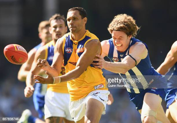 Josh Hill of the Eagles handballs whilst being tackled by Ben Brown of the Kangaroos during the round one AFL match between the North Melbourne...