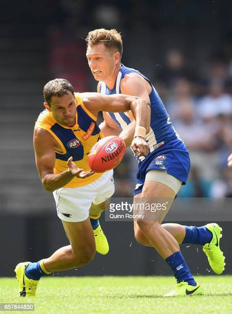 Josh Hill of the Eagles handballs whilst being tackled by Shaun Higgins of the Kangaroos during the round one AFL match between the North Melbourne...