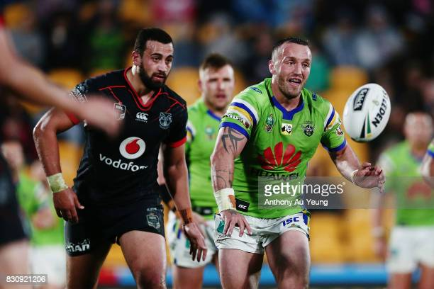 Josh Hodgson of the Raiders gets a pass away against Ben Matulino of the Warriors during the round 23 NRL match between the New Zealand Warriors and...