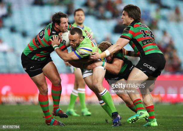 Josh Hodgson of the Raiders is tackled by the Rabbitohs defence during the round 21 NRL match between the South Sydney Rabbitohs and the Canberra...