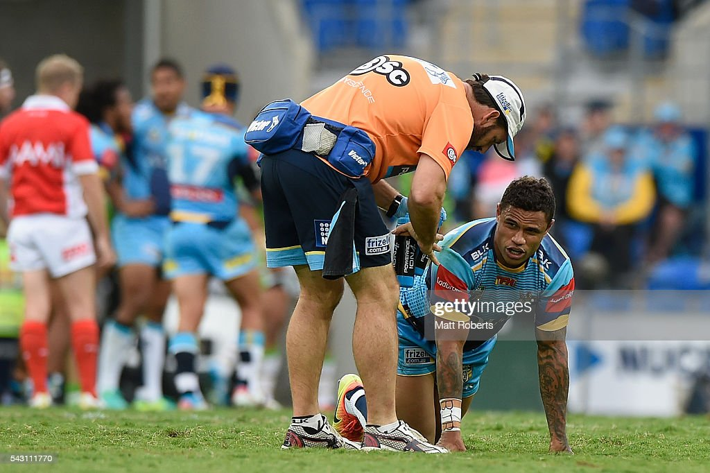 Josh Hoffman of the Titans receives attention on the field during the round 16 NRL match between the Gold Coast Titans and the Canberra Raiders at Cbus Super Stadium on June 26, 2016 in Gold Coast, Australia.