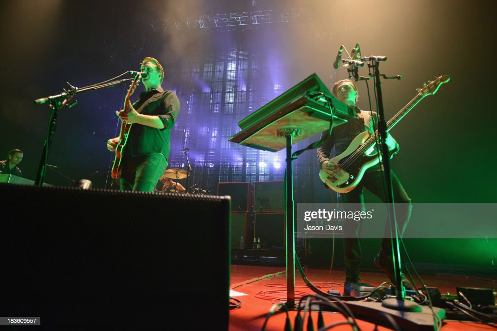Josh Homme and Michael Shuman of Queens of the Stone Age perform at Nashville Municipal Auditorium on October 7, 2013 in Nashville, Tennessee.
