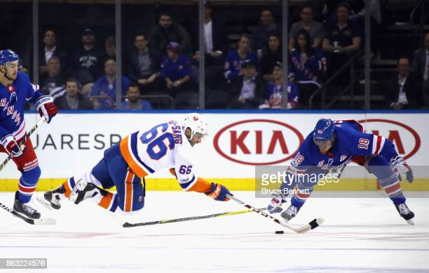 Josh HoSang of the New York Islanders is tripped up as he shoots against Marc Staal of the New York Rangers during the second period at Madison...