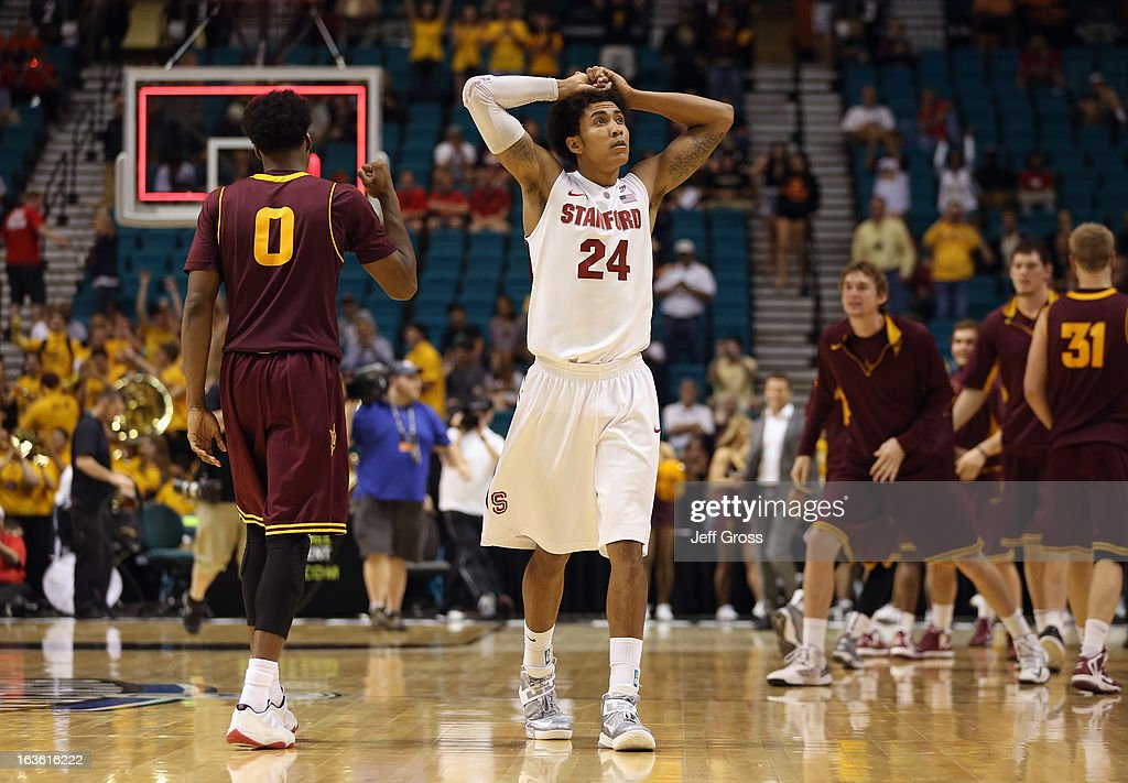 Josh Huestis #24 of the Stanford Cardinal is dejected following his teams 89-88 overtime loss, as Carrick Felix (L) #0 of the Arizona State Sun Devils celebrates during the first round of the Pac 12 Tournament at the MGM Grand Garden Arena on March 13, 2013 in Las Vegas, Nevada.